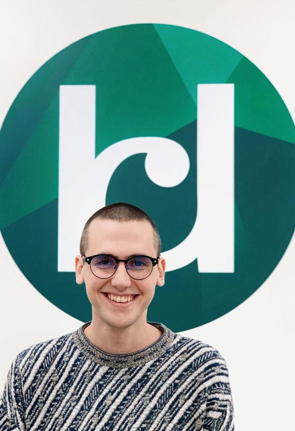 James in front of Katy Dwyer Design Logo